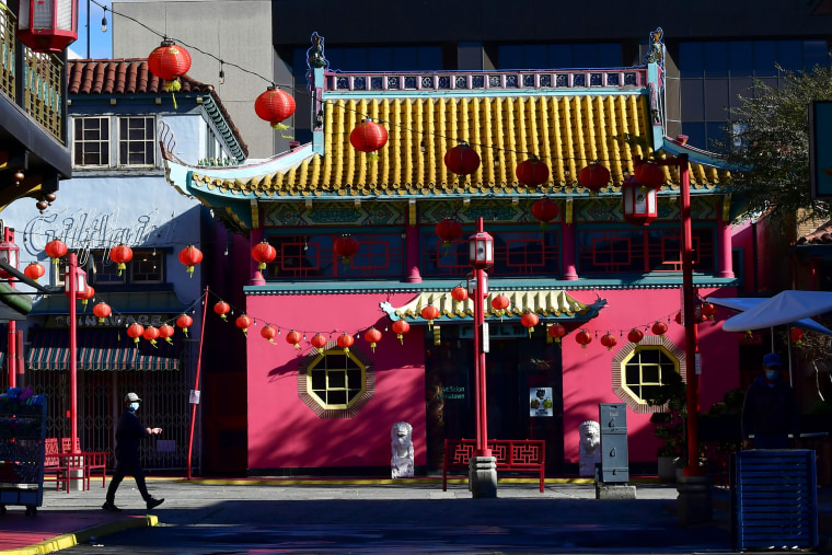 Image: A pedestrian walks across a deserted Chinatown Central Plaza decorated with red lanterns on the first day of the Lunar New Year in Los Angeles on Feb. 12, 2021.