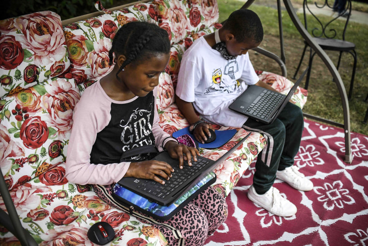 Fourth-grader Sammiayah Thompson, left, and her brother, third-grader Nehemiah Thompson, work outside in their yard on laptops provided by their school system for distant learning in Hartford, Conn., on June 5, 2020.