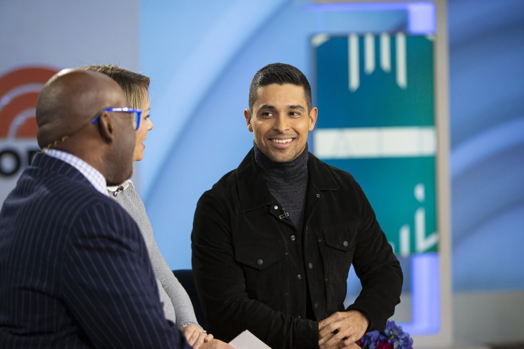 Wilmer Valderrama in a gray turtleneck and black jacket on the set of TODAY
