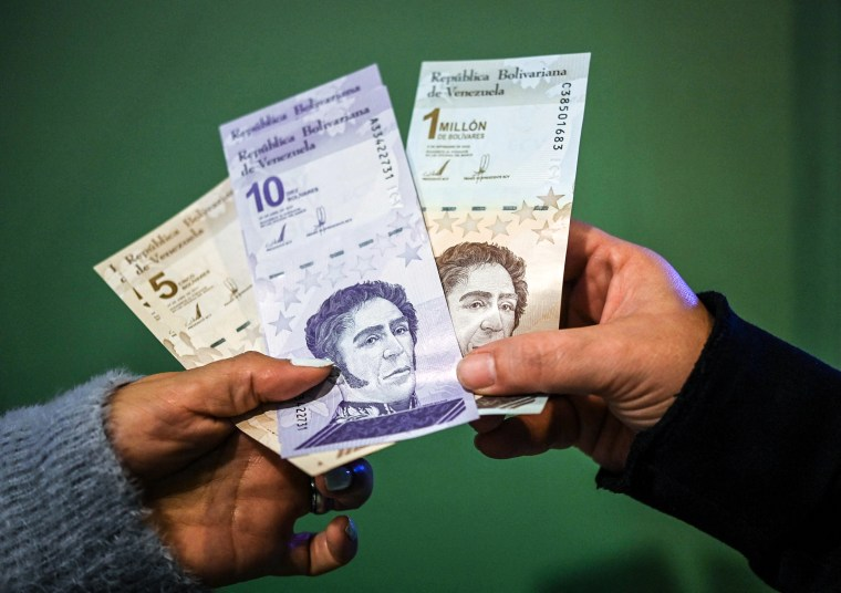 Image: People show the new five and ten bolivar bank notes put in circulation by the Central Bank of Venezuela as part of the currency reconversion, and another of one million bolivares that will continue to circulate with a value of one bolivar, after making a cash withdrawal at an ATM in Caracas on Oct. 1, 2021.