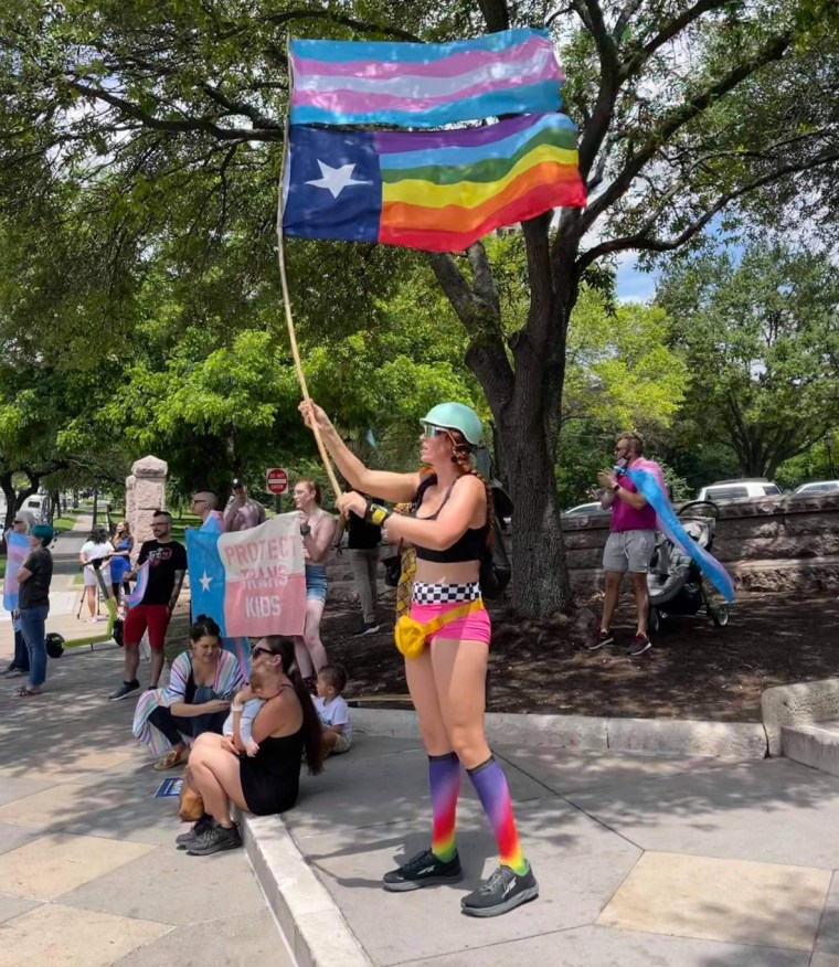 The Rev. Remington Johnson waves pride flags at a rally in Austin in May.