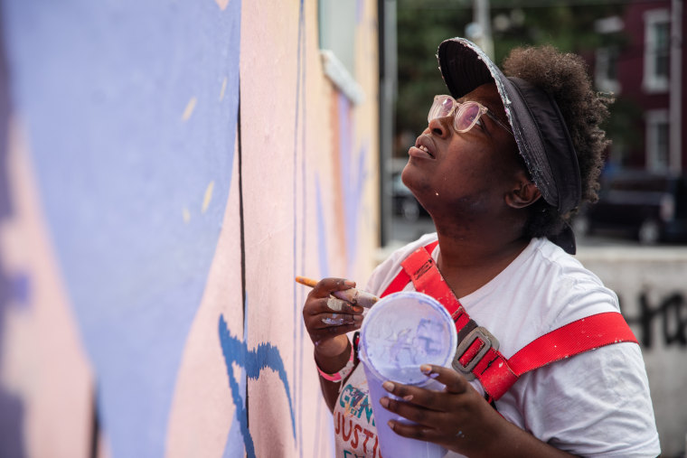 A painter works on the We Are Universal mural on Sept. 8, 2021 in Philadelphia.