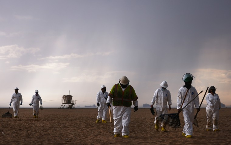 Image: Cleanup workers in protective suits depart the closed Huntington State Beach as a storm approaches after a 126,000-gallon oil spill from an offshore oil platform on Oct. 4, 2021 in Huntington Beach, Calif.
