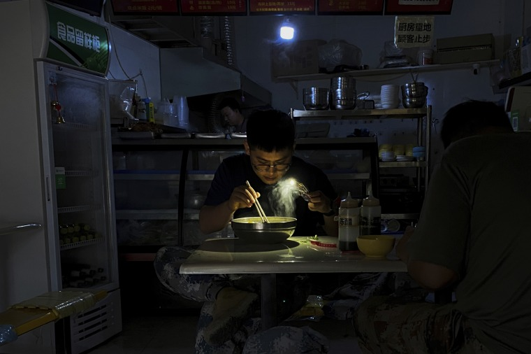 A man uses his smartphone flashlight to light up his bowl of noodles at a restaurant during a blackout in northeastern China.