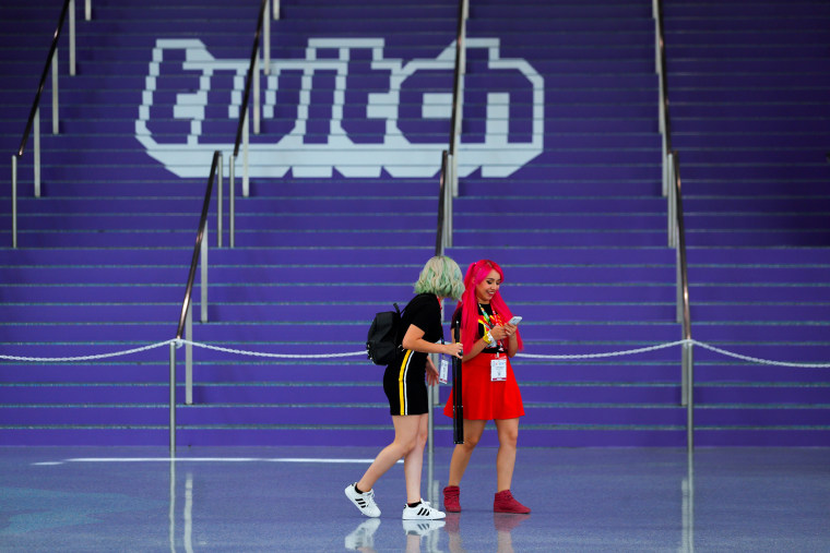 Image: Attendees walk past a Twitch logo painted on stairs during opening day of E3 in Los Angeles on June 11, 2019.