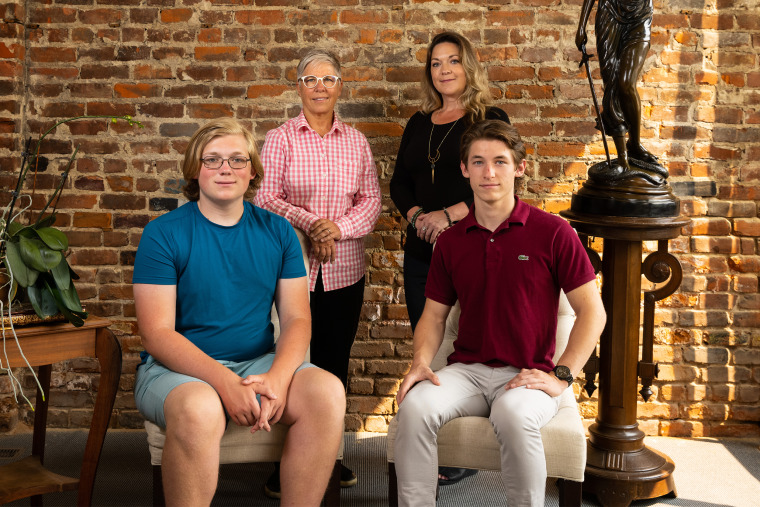 Erin Porterfield, back left, and Kristin Williams, back right, along with their children, Cameron Porter Williams, 16, front left, and Kadin Porter Williams, 18, at Omaha family law firm Koenig | Dunne in Omaha, Neb. on Aug. 4, 2021.