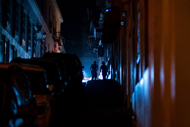 Image: People walk in a street left in darkness by a power outage following a cyber attack cyberattack in Old San Juan, Puerto Rico, on June 10, 2021.