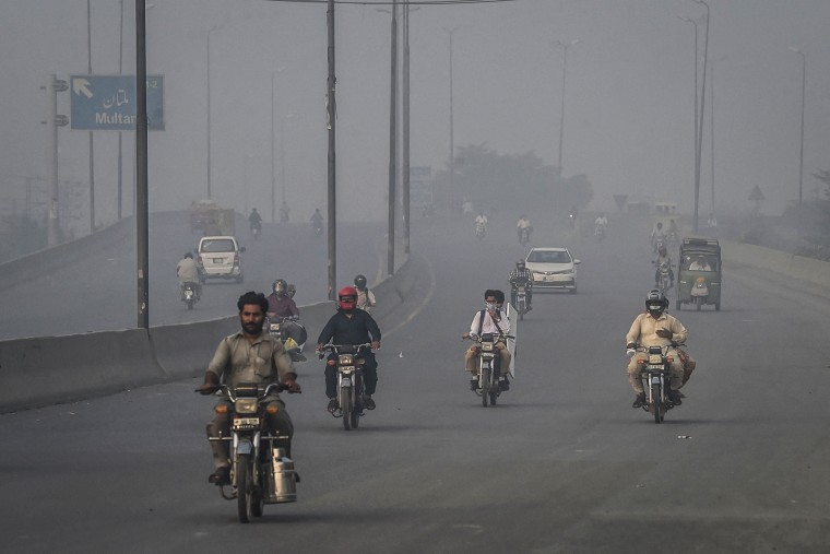 Image: Commuters ride along a road under smog and fog conditions in Lahore on Oct. 6, 2021.