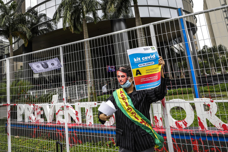 Image: A demonstrator in a Brazilian President Jair Bolsonaro mask protests against the Prevent Senior health care company outside its headquarters in Sao Paulo, Brazil on Sept. 30, 2021.