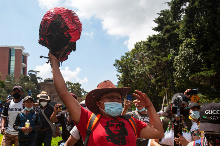 A demonstrator holds a head torn off from the statue of former President Jose Maria Reina Barrios during protests against the treatment of indigenous people by European conquerors during Hispanic Heritage Day in Guatemala City, Guatemala, on Oct. 12, 2021.
