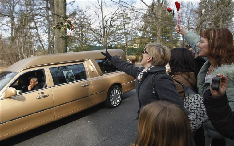 New Jersey fans wave at Whitney Houston's hearse as it proceeds to the cemetery in New Jersey on Feb. 19.