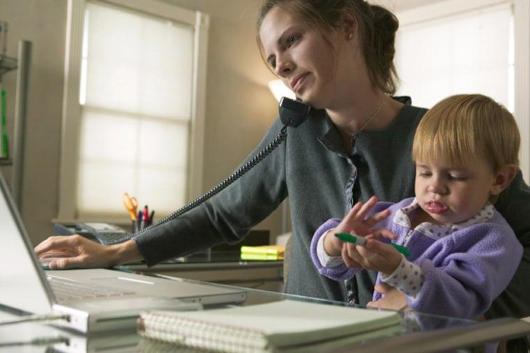 A mother multitasks at her computer.