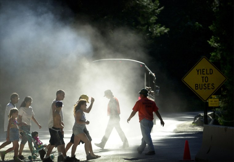 Pedestrians walk through a cloud of dust and diesel exhaust from a transit bus near Yosemite Village on June 16, 2000, in Yosemite National Park.