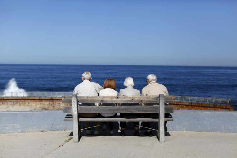 A pair of elderly couples view the ocean and waves along the beach in La Jolla, Calif. More couples over 50 are living together (minus the marriage certificate) and for many money is a big factor.
