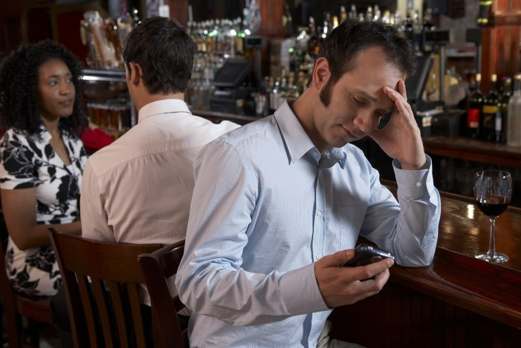 Frustrated man holding mobile phone at bar