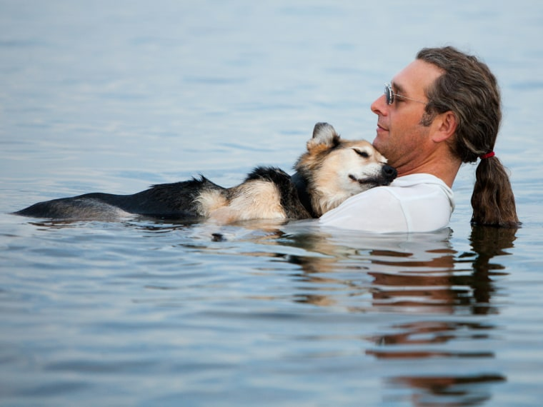 In loving arms: Man floats his sick dog to sleep, becomes