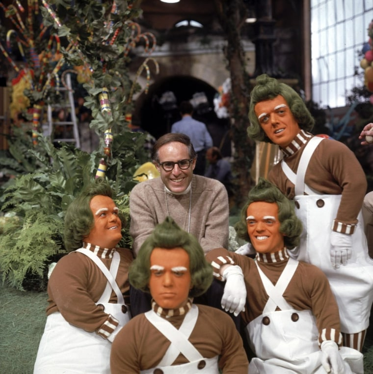 """Mel Stuart, director of the 1971 film \""""Willy Wonka & the Chocolate Factory,\"""" poses with the Oompa Loompas characters on the set of the film."""