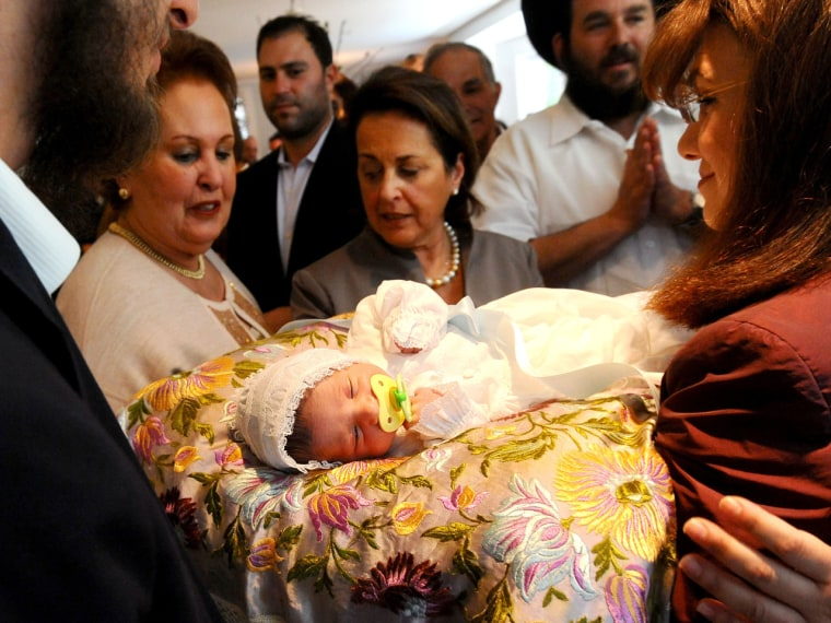 Benjamin Abecassis rests on a pillow surrounded by family members immediately following his bris, a Jewish circumcision ceremony in San Francisco. The nation's top pediatrician's group said the health benefits of procedure outweigh the risks, but stopped short of recommending it.
