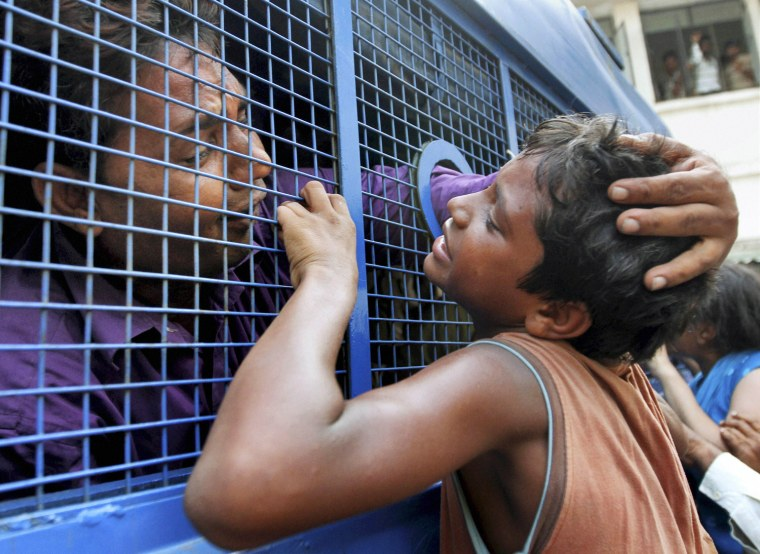 A convict consoles his son while being taken to prison after a court verdict in a 2002 religious violence case, in Ahmadabad, India, Aug. 29, 2012. The court in western India found 32 people guilty of charges ranging from murder to rioting for their part in the deadly religious violence.  The religious violence began following a train fire on Feb. 27, 2002, that killed 60 Hindu pilgrims. Muslims were blamed for the fire, leading to weeks of rioting in which Hindu mobs rampaged through towns and villages burning Muslim homes and businesses.