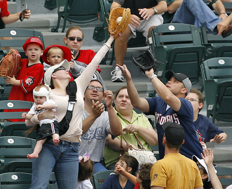 Tiffany Goodwin, of  Fredericksburg Va., robs her husband Allen, at right with glove, of a foul ball while holding 8-month-old son Jerry, during a minor league baseball game in Richmond Va.