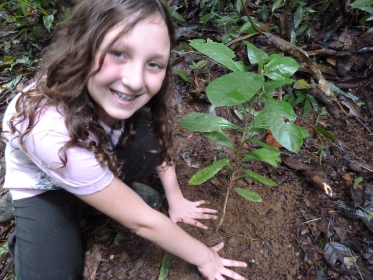 Jennifer Miner's daughter, Jessica, plants a sapling in Costa Rica as part of a reforestation effort.
