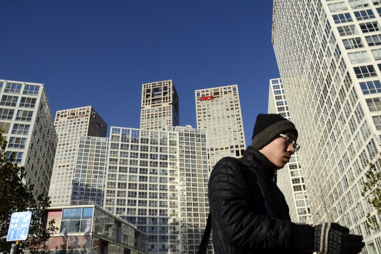 A Chinese man walks in the central business district in Beijing on November 30, 2012. China's economy is likely to pull ahead of the U.S. economy in l...