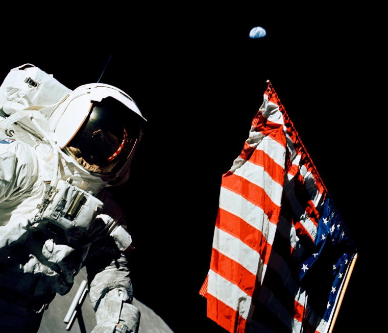 Apollo 17 astronaut Harrison Schmitt faces the American flag on the lunar surface with Earth in the black sky above, during a moonwalk on Dec. 12, 1972.