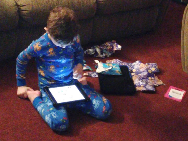 Ethan Funk looks at the iPad he got on the first night of Hanukkah.