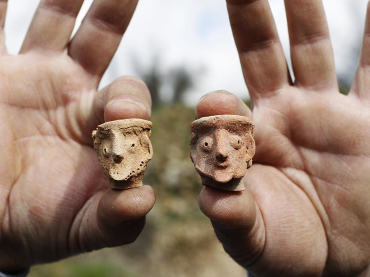 An employee of the Israeli Antiquities Authority displays figurines at Tel Motza archaeological site on the outskirts of Jerusalem.