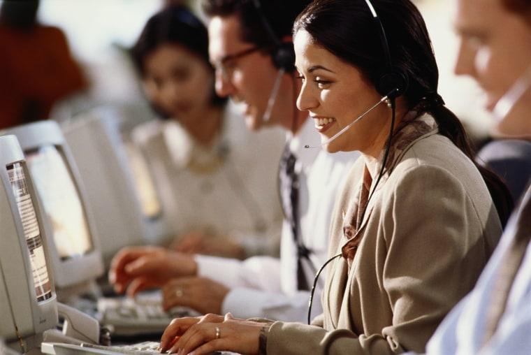 Customer service operators at work, using telephone headsets