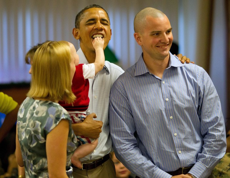epa03043130 Eight month old Cooper Wall Wagner sticks his fingers in US President Barack Obama's mouth as the President (C) poses for a picture with Cooper's parents Greg (R) and Meredith Wagner (L) in Kaneohe, Hawaii 25 December 2011. The President and Mrs. Obama make their annual trip to greet current and retired members of the US military and their families as they eat a Christmas Day meal Anderson Hall mess hall at Marine Corps Base Hawaii. EPA/Kent Nishimura / POOL