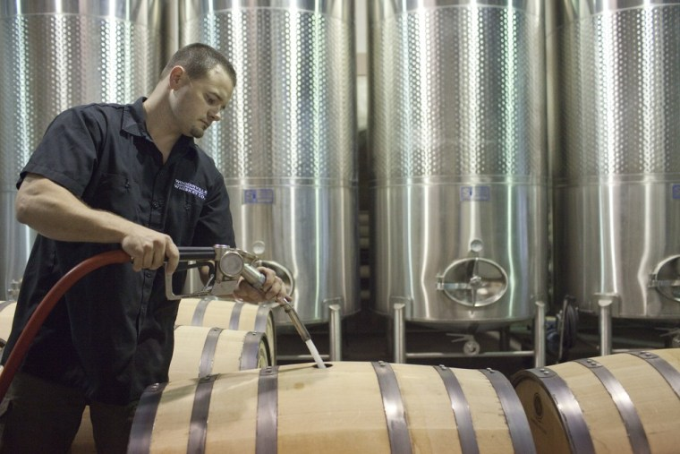 Brett Carlile, co-owner of Woodinville Whiskey Co., fills a barrel with unaged whiskey.