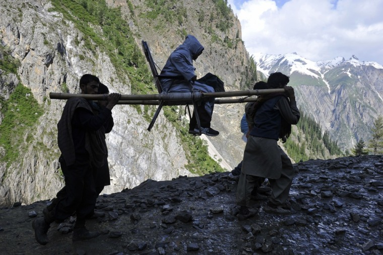A Hindu devotee is carried by porters during her pilgrimage from Baltal Base Camp to the holy Amarnath Cave Shrine, in Baltal on June 25.