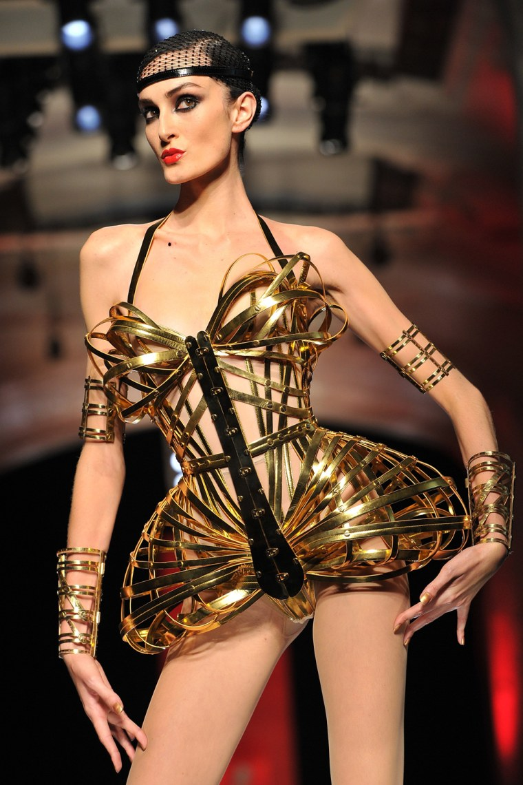 A model at Gaultier's show steps out in a gold corset, hair net, and not much more.