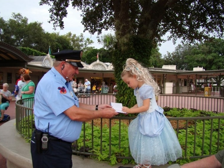 """This photo of Walt Disney security guard Freddie Wieczorek getting an autograph from 5-year-old \""""princess\"""" Alli Bunchuk recently went viral."""