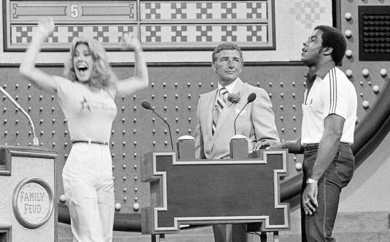 "Richard Dawson, center, during a taping of ""Family Feud"" in 1980 with Dallas Cowboys running back Tony Dorsett and Cowboys cheerleader Suzette Scholz-Derrick."