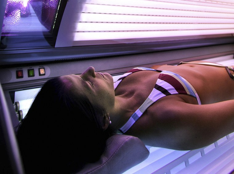 A woman lies in a tanning booth in Anchorage, Alaska, in this 2005 file photo.