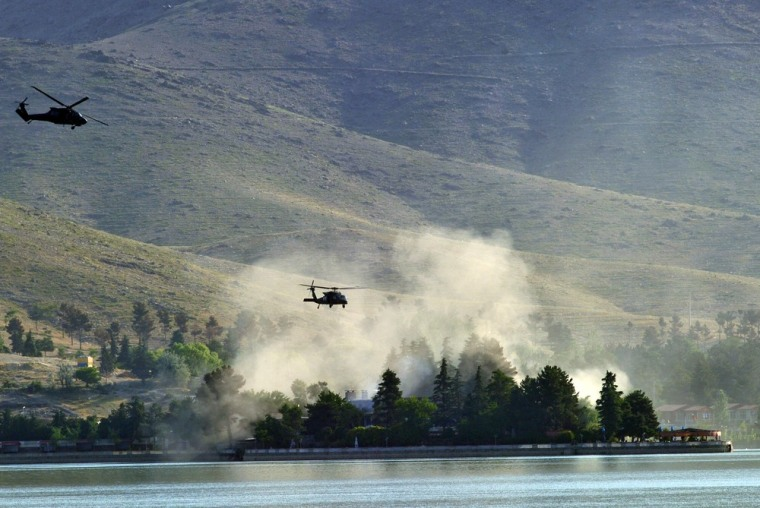 NATO UH-60 Black Hawk helicopters fly near the Spozhmai Hotel in Qargha lake in the outskirts of Kabul in the early hours of Friday.
