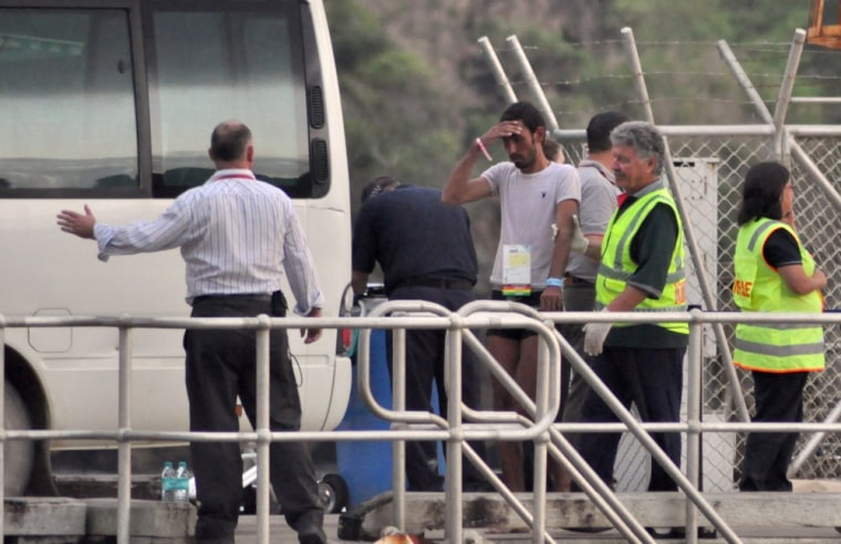 People rescued after their boat capsized north of Australia arrive at Christmas Island Friday.