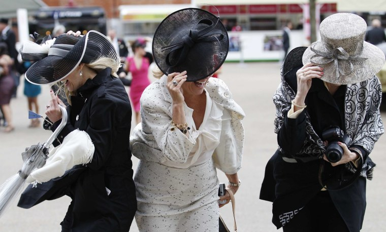 Race goers struggle to keep their hats on in strong winds on the fourth day at Royal Ascot, southwest of London, on June 22.