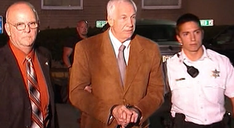 Jerry Sandusky is led from the Centre County Courthouse in handcuffs Friday night.