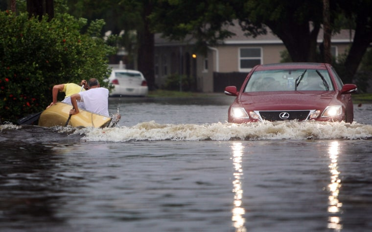 Wake from a car passing by causes canoe-paddlers to capsize in St.Petersburg, Fla., as flooding continues to worsen and Tropical Storm Debby pounds the Tampa Bay area.