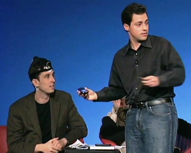 Neuroscientist Philip Low (at right) demonstrates how the iBrain device can send brain-wave readings to a cellphone with an subject who's wearing the headband (at left) during a TEDMED 2009 presentation. Click on the image to watch the YouTube clip.