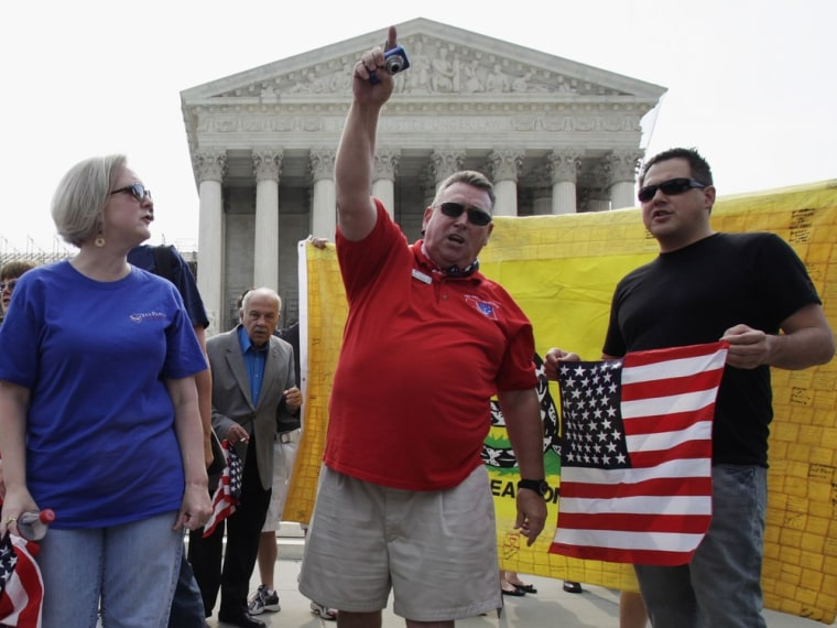 People protest against President Obama's health care reform in front of U.S. Supreme Court in Washington June 25.