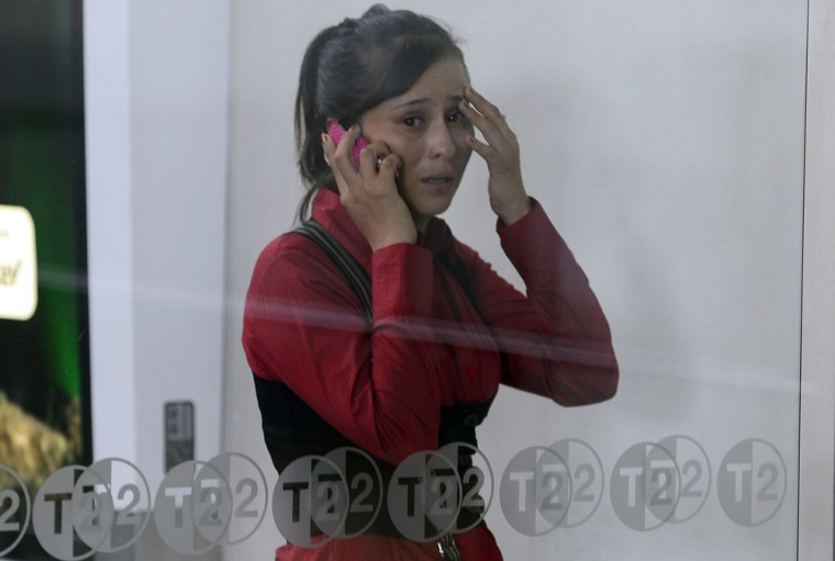A passenger speaks on her cellphone at Benito Juarez international airport Terminal 2, in Mexico City, where two police officers were shot dead and a third was wounded on Monday.