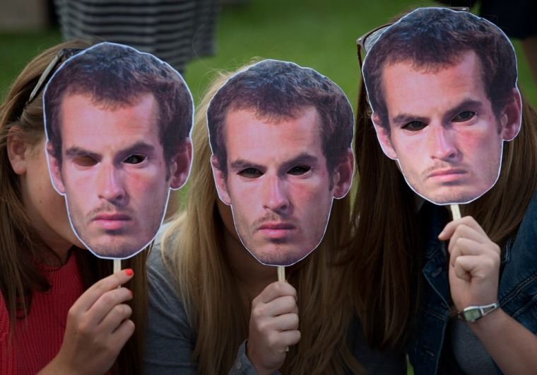 Tennis fans pose for pictures with Andy Murray masks as they queue for tickets.