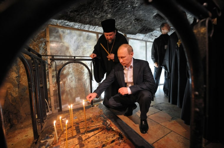 Russian President Vladimir Putin lights a candle during his visit to the Church of the Holy Sepulchre, in the old city of Jerusalem on June 26.