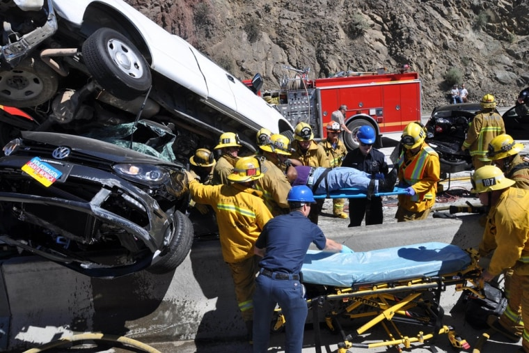 Firefighting paramedics remove an injured motorist on Tuesday at the site of a freewaypileup in northern Los Angeles County involving at least 19 vehicles.