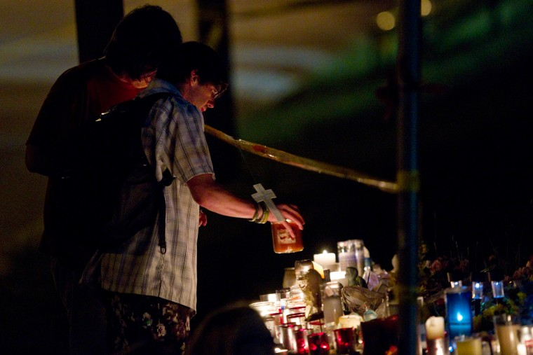 Local residents light candles at a memorial while rescue workers wait to access the wreckage of the Algo Centre Mall in Elliot Lake, Ontario, Canada on June 27. Officials recovered a body Wednesday after spending the night dismantling a partially collapsed Ontario mall in a renewed rescue effort after angry residents had shouted down fears that the unstable structure made the work too risky to continue. Part of the roof collapsed last Saturday afternoon. At least 22 people had minor injuries.