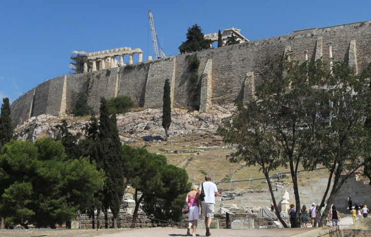 Tourists visit the archaeological site immediately beneath the south side of the Athens Acropolis where a 42-year-old bank employee reportedly committed suicide Thursday.
